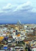 stock photo of urbanisation  - Aerial view of the city of Sevilla are the roofs of the buildings next to Each Other it is a cloudy day - JPG