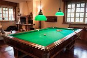 image of snooker  - Billiard table with mock tiger skin rug on parquet floor