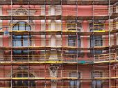 stock photo of scaffold  - Old house being repaired with scaffolding in front. 