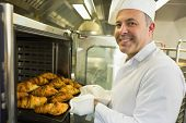 stock photo of croissant  - Mature baker smiling proudly at the camera take some croissants out of oven - JPG
