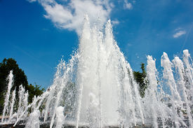 foto of ejaculation  - Water jet in a city park fountain with clear blue sky as background - JPG