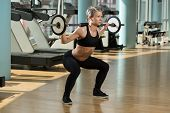 stock photo of squatting  - Beautiful Fit Woman Doing Barbell Squats In The Gym - JPG