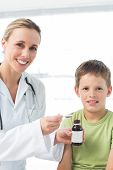 Portrait of happy female doctor giving little boy cough syrup in hospital
