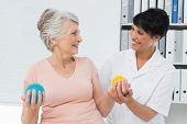 foto of stress-ball  - Female doctor with senior patient using stress buster balls at the medical office - JPG