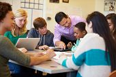 stock photo of tutor  - High School Students With Teacher In Class Using Laptops - JPG
