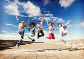 summer, sport, dancing and teenage lifestyle concept - group of teenagers jumping