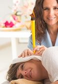picture of ear candle  - terapist doing ear candling on beautiful woman - JPG