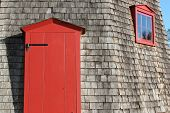 stock photo of red siding  - weathered wood siding with red door and window on old windmill - JPG