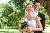 stock photo of half-dressed  - Portrait of newly wed couple with flower bouquet in park - JPG