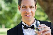 Closeup portrait of young groom drinking champagne in garden