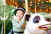pic of merry-go-round  - cheerful smiling little boy having fun at the merry - JPG