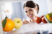 foto of refrigerator  - Attractive woman smiling and holding a glass of milk in front of refrigerator - JPG