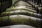 stock photo of whiskey  - whiskey or wine barrels stacked in winery - JPG