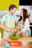 Married Smiling Couple Cooking Apple Pie At The Kitchen At Home