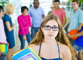 stock photo of saddening  - Sad Student with Glasses Holding Books - JPG