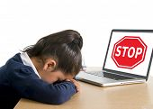 picture of stop bully  - hispanic sweet little girl crying and suffering internet bullying and abuse at school sitting at desk with computer and stop sign - JPG