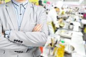 stock photo of catering service  - Business Man standing against the Background of Kitchen as Concept of Restaurant Catering or Food service - JPG