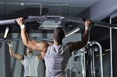 stock photo of pull up  - Handsome Muscular Male Model With Perfect Body Doing Pull Ups - JPG