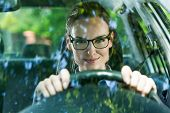 pic of seatbelt  - Young attractive woman in glasses driving a car - JPG