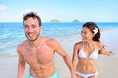 stock photo of body shapes  - Happy couple having fun on beach vacation during summer holiday - JPG