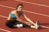 stock photo of stretching exercises  - Beautiful Young Woman in Sports Bra Stretching Leg Muscles on Track - JPG