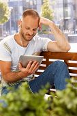 stock photo of sitting a bench  - Young man sitting outdoors on a bench - JPG
