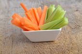 picture of celery  - Bowl of carrot and celery sticks on wooden background - JPG