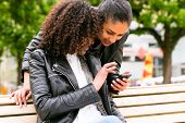 picture of bff  - Two north African teen friends reading and writing text message on mobile phone in park   - JPG