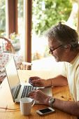 stock photo of card-making  - Mature Man Making On Line Purchase Using Credit Card - JPG