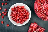 foto of pomegranate  - Red pomegranate seeds in a white bowl on table - JPG
