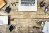 stock photo of hard-on  - Mix of office supplies and gadgets on a wooden desk background - JPG