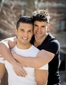 stock photo of fitness man body  - young happy attractive gay men couple with strong fit body cuddling posing outdoors on street in sexual freedom and free homosexual love concept in urban background - JPG