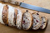 stock photo of fresh slice bread  - A sliced loaf of fresh cranberry walnut bread and a bread knife - JPG