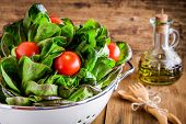 stock photo of iceberg lettuce  - fresh green organic lettuce with cherry tomatoes on a wooden rustic background - JPG
