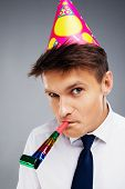 stock photo of office party  - Funny close up photo of young office manager with party hat and blower - JPG