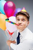 pic of office party  - Funny close up photo of young office manager with party hat and blower - JPG