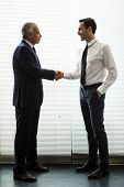 stock photo of 55-60 years old  - Full length portrait of two businessmen standing up smiling and shaking hands - JPG