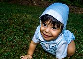 stock photo of crawl  - Close up shot of smiling latino baby dressed up and crawling outside in the grass - JPG