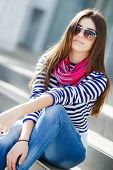 stock photo of straight jacket  - Beautiful young girl, Caucasian appearance, with dark, long, straight hair, sun glasses, wearing a striped shirt, jeans wearing pink neck scarf, sitting outdoors on stairs in the city.