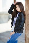 stock photo of straight jacket  - Beautiful young girl, Caucasian appearance, with dark, long, straight hair, brown eyes and beautiful dark eyebrows, wearing a striped shirt, blue jeans and black leather jacket, standing in the street, leaning against a wooden pole.