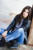 foto of straight jacket  - Beautiful young girl, Caucasian appearance, with dark, long, straight hair, brown eyes and beautiful dark eyebrows, wearing a striped shirt, blue jeans and black leather jacket, sitting on the street on the sidewalk