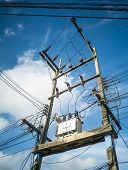 stock photo of untidiness  - Electricity post and the transformer with untidy wires on cloudy sky