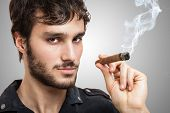 foto of cigar  - Portrait of a confident man smoking a cigar - JPG