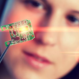 image of microchips  - Girl shows new microchip on plate  that can be implanted into a paralyzed patient - JPG