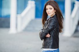 image of jacket  - Beautiful young girl, Caucasian appearance, with dark, long, straight hair, brown eyes and beautiful dark eyebrows, wearing a striped shirt, blue jeans and black leather jacket, standing in the street, near the blue building with white railings [[** Note - JPG