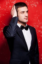 foto of bow tie hair  - Handsome young man in suit and bow tie touching his hair and looking away while standing against red background - JPG
