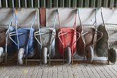 picture of wheelbarrow  - six old and rusty wheelbarrows rest against wall of farm barn - JPG