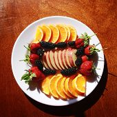 stock photo of mulberry  - Plate with pieces of orange and apple - JPG