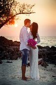 image of barefoot  - brunette bride and handsome groom barefoot hug at sand beach at sunrise - JPG