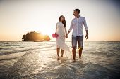 picture of barefoot  - bride and groom walk barefoot in shallow water at spit against sunrise - JPG